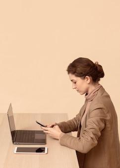 Mulher sentada ao lado de seu laptop e usando o smartphone