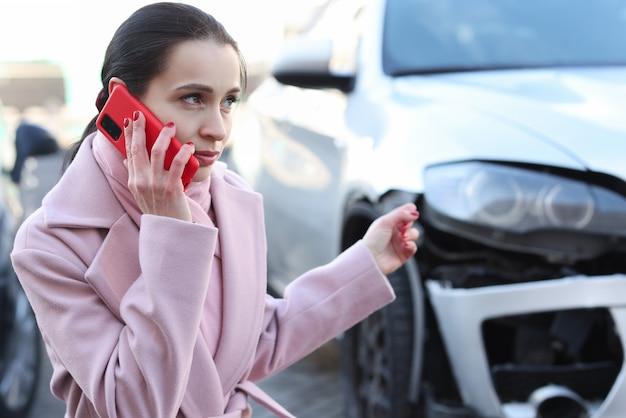 Mulher sentada ao lado de um carro acidentado e falando no smartphone
