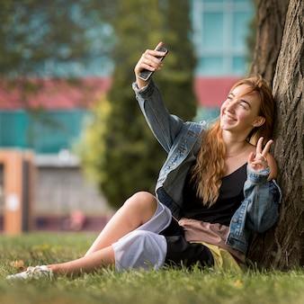 Mulher sentada ao lado de uma árvore tirando uma selfie