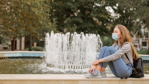 Mulher sentada ao lado de uma fonte com máscara médica