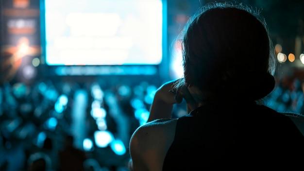Mulher sentada assistindo futebol em um lugar público à noite