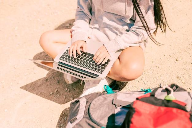Mulher sentada com as pernas cruzadas na estrada e trabalhando no laptop