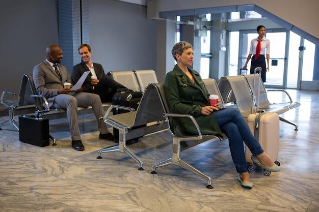 Mulher sentada com bagagem na sala de espera
