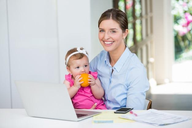 Mulher sentada com o bebê por mesa