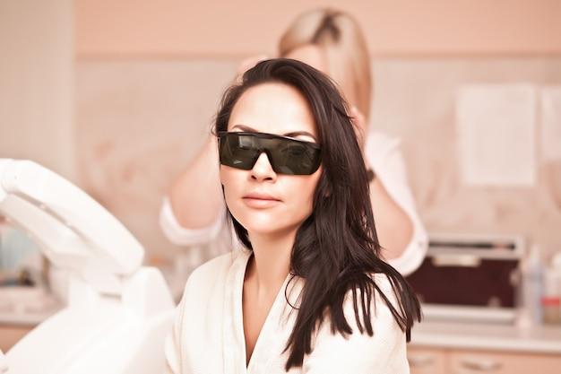 Mulher sentada com óculos de proteção nos olhos faz um tratamento de pele a laser. salão de beleza spa.