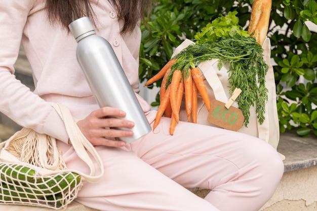 Mulher sentada com sacos reutilizáveis com comida