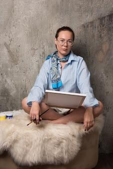 Mulher sentada com tela e escova sobre fundo de mármore.