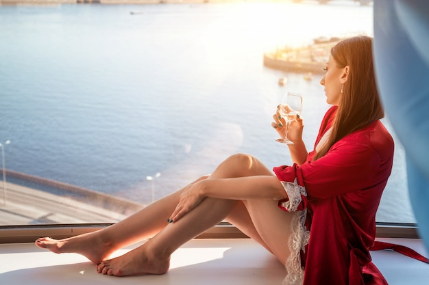 Mulher sentada com um copo de vinho na janela, apreciando a vista da janela