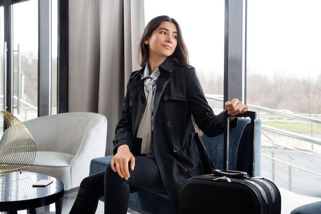 Mulher sentada com uma mala no saguão do hotel ou no saguão do aeroporto