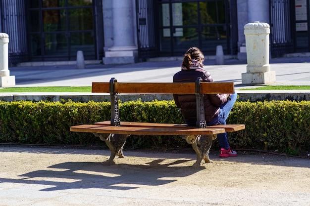 Mulher sentada de costas em um banco de um parque público, desfrutando de um dia ensolarado. madrid.