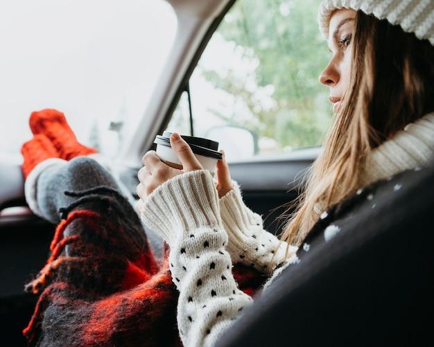 Mulher sentada de lado em um carro tomando uma xícara de café