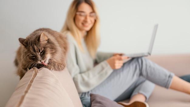 Mulher sentada dentro de casa com seu gato