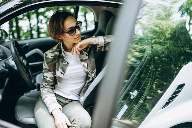 Mulher sentada dentro de um carro na floresta