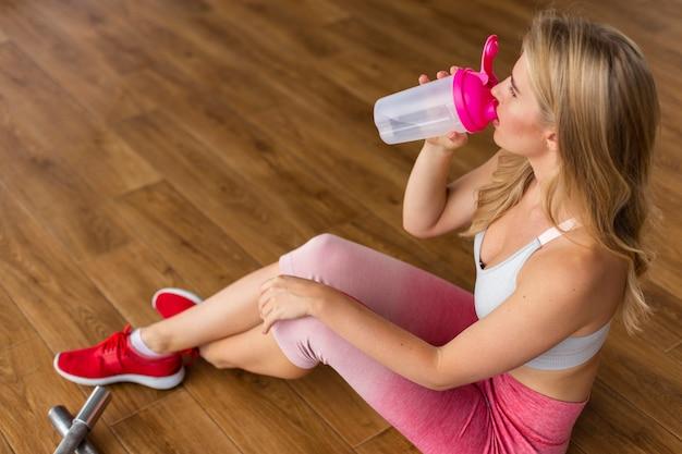 Mulher sentada e bebendo água