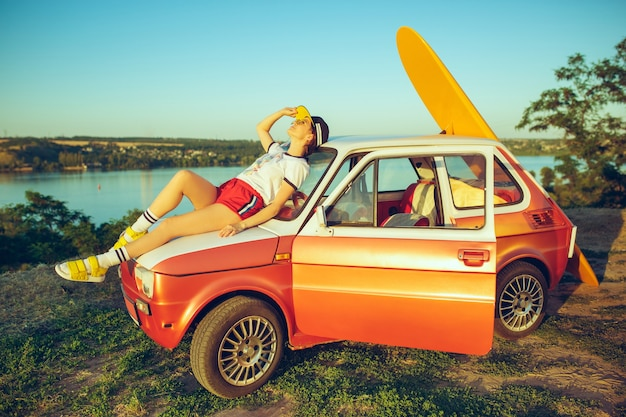 Mulher sentada e descansando no carro na praia num dia de verão perto do rio.