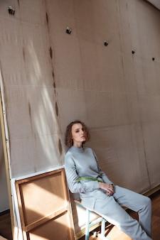 Mulher sentada e encostada em um pano de fundo de lona