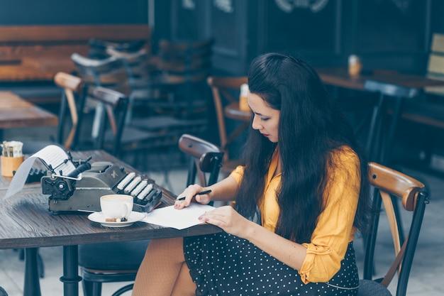 Mulher sentada e escrevendo algo no papel e pensativo e em amarelo top e saia longa no terraço do café durante o dia.