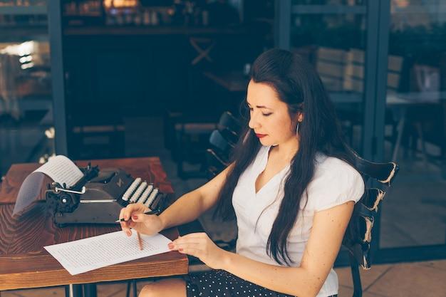 Mulher sentada e escrevendo no papel no terraço do café em camisa branca durante o dia