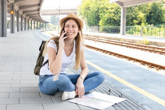 Mulher sentada e falando no chão