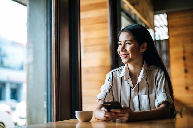 Mulher sentada e jogando seu telefone inteligente no café