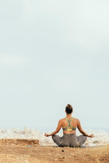 Mulher sentada e meditando na natureza