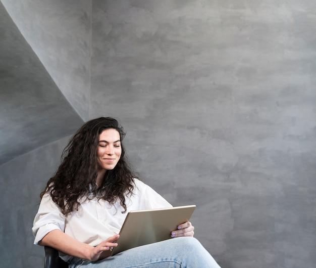 Mulher sentada e olhando para o laptop