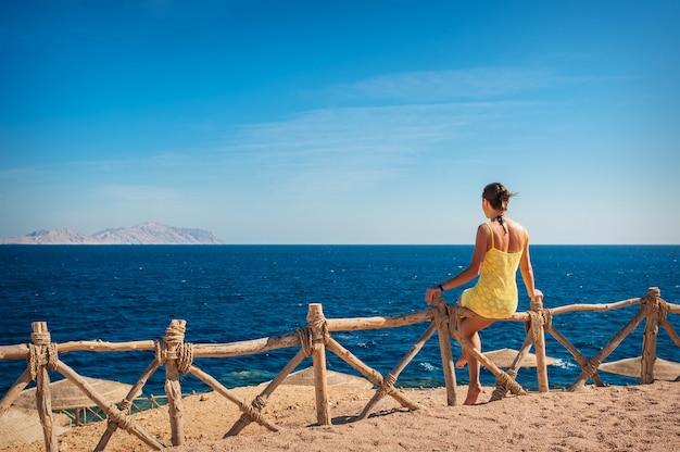 Mulher sentada e olhando para o mar