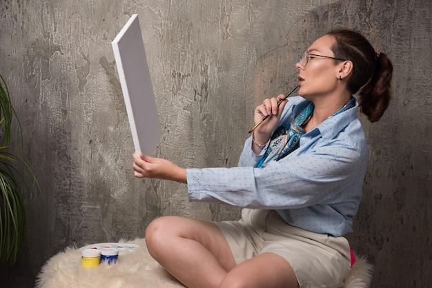 Mulher sentada e olhando para uma tela com um pincel sobre fundo de mármore
