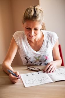 Mulher sentada e resolvendo palavras cruzadas