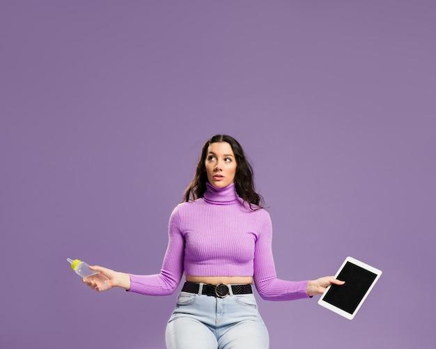 Mulher sentada e segurando a mamadeira e tablet digital