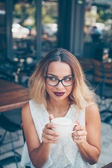 Mulher sentada e segurando café e camisa branca texturizada no terraço do café durante o dia.