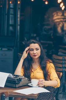 Mulher sentada e segurando o café no terraço do café em amarelo top e saia longa durante o dia e pensativo