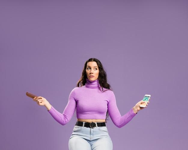 Mulher sentada e segurando o telefone móvel e pente