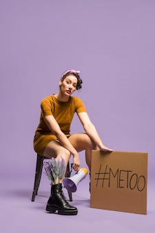 Mulher sentada e segurando papelão