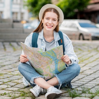 Mulher sentada e segurando um mapa
