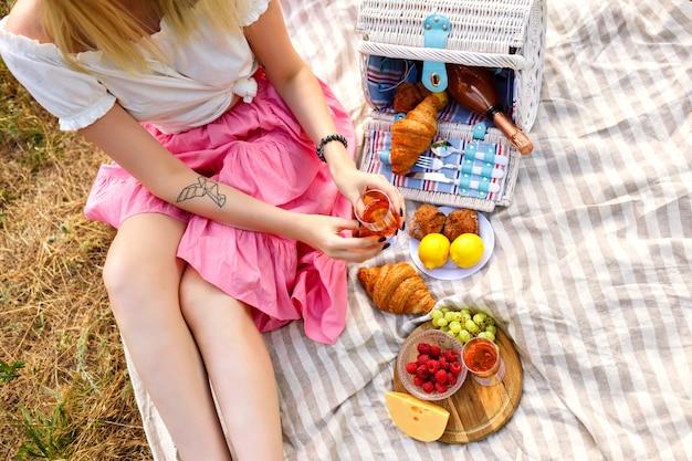 Mulher sentada e segurando uma taça de champanhe, frutas tradicionais, croissants e queijo,