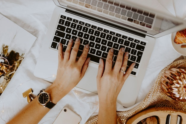 Mulher sentada e trabalhando com seu laptop na cama