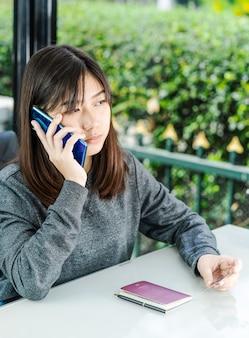 Mulher sentada e usando o smartphone para compras on-line com cartão de crédito e passaporte no convés no escritório em casa