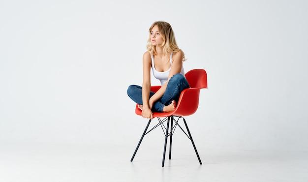 Mulher sentada em cadeiras vermelhas posando glamour, moda, estilo de vida