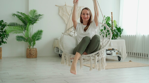 Mulher sentada em casa balançando em um balanço sentado em casa.