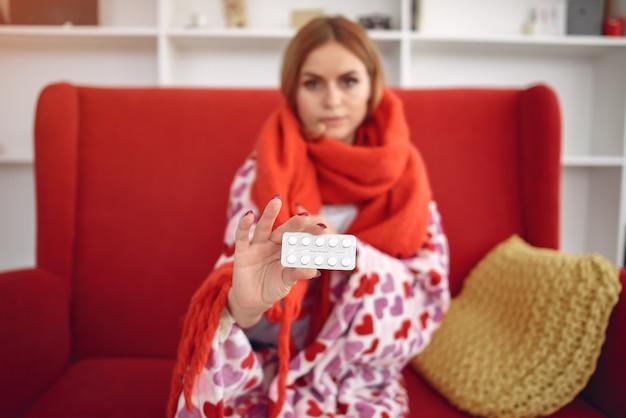 Mulher sentada em casa com um resfriado e tomando pílulas