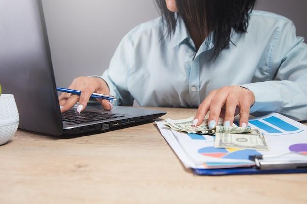 Mulher sentada em frente à mesa de trabalho, estudando papéis e dados