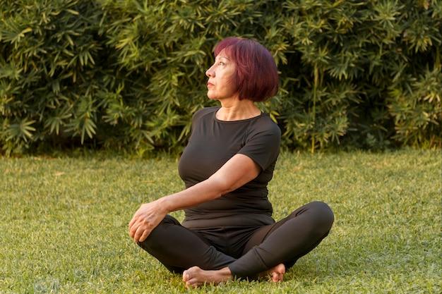 Mulher sentada em posição de ioga e fazendo exercícios para trás