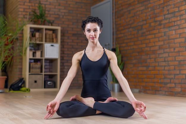 Mulher sentada em posição de lótus fazendo ioga em casa