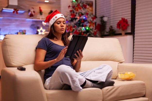 Mulher sentada em posição de lótus no sofá na cozinha decorada de natal