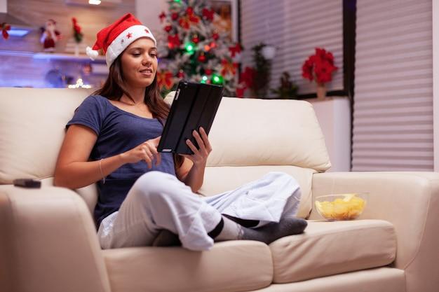 Mulher sentada em posição de lótus no sofá navegando nas redes sociais escrevendo e-mail de natal
