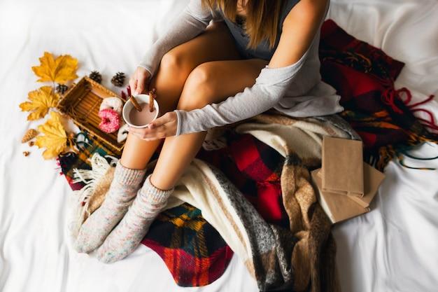 Mulher sentada em sua cama com livros e bebendo café com canela, biscoitos e donuts com glacê.
