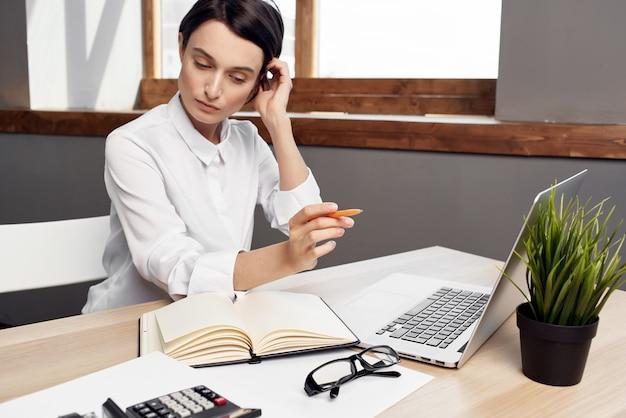 Mulher sentada em sua mesa no escritório na frente de um executivo profissional trabalhando com laptop