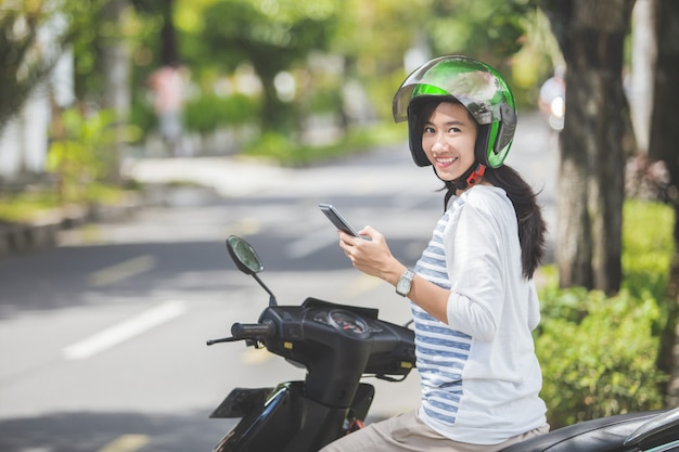 Mulher sentada em sua moto e usando telefone celular