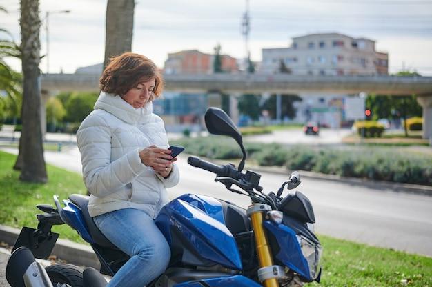 Mulher sentada em sua motocicleta estacionada, consulta seu celular